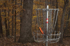 Disc Golf. Basket for Disc Golf in a Forest during Fall Colors. An orange disc is in the basket Stock Photo