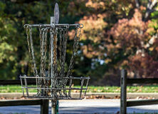 Disc Golf Basket by Street. A disc golf basket in front of a street waits to catch a putter royalty free stock image