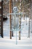 Disc golf basket in winter. Disc golf basket in snowy landscape Stock Photo