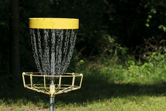Disc Golf Goal Target In The Woods. A single disc golf (frisbee golf) permanent metal goal target in a sunny opening in the woods. The space on the right side Royalty Free Stock Photo