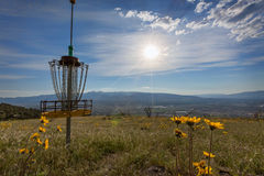 Disc golf metal hoop basket landscape view sunny day wildflowers. Disc golf metal hoop basket with landscape viewpoint sunburst sunny day wildflowers blue sky Royalty Free Stock Photography