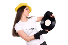 Disc jockey. Beautiful young woman disc jockey with yellow hat on head holding disc recording royalty free stock photos