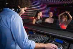Disc jockey de sexo masculino que juega música con tres mujeres que bailan en la sala de baile Fotografía de archivo