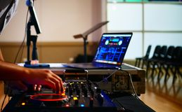 Disc jockey with equipment. Disc jockey working and managing and controlling a turntable and laptop to play dance music at an entertainment event. It is dark and stock image