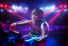 Disc jockey girl playing music with light beam effects on stage. Pretty young disc jockey girl playing music with light beam effects on stage Stock Image