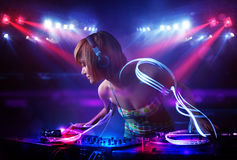 Disc jockey girl playing music with light beam effects on stage Royalty Free Stock Photos