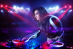 Disc jockey girl playing music with light beam effects on stage Stock Image