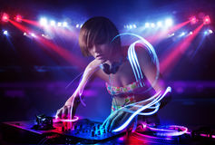 Disc jockey girl playing music with light beam effects on stage. Pretty young disc jockey girl playing music with light beam effects on stage Stock Photos