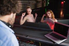 Disc jockey maschio che gioca musica con due donne che ballano sulla pista da ballo Fotografie Stock Libere da Diritti
