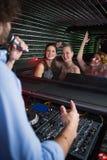 Disc jockey maschio che gioca musica con tre donne che ballano sulla pista da ballo Immagini Stock