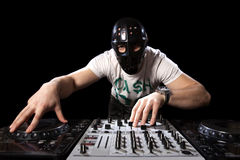 Disc jockey with mask mixing music Royalty Free Stock Image