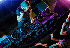 Disc jockey mixing electronic music in club. Shot from aerial percspective. People are dancing stock images