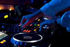Disc jockey mixing music. Close up view of the hands of a male disc jockey mixing music on his deck with his hands poised over the vinyl record on the turntable stock image