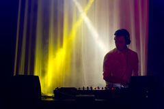 Disc jockey mixing music in a nightclub. Standing at his deck silhouetted by colourful spotlights Royalty Free Stock Images