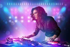 Disc jockey mixing music on turntables on stage with lights and Stock Photography