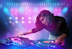 Disc jockey mixing music on turntables on stage with lights and Royalty Free Stock Photos