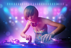 Disc jockey mixing music on turntables on stage with lights and Royalty Free Stock Image