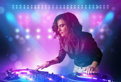 Disc jockey mixing music on turntables on stage with lights and. Pretty young disc jockey mixing music on turntables on stage with lights and stroboscopes Royalty Free Stock Image
