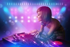 Disc jockey mixing music on turntables on stage with lights and stroboscopes. Pretty young disc jockey mixing music on turntables on stage with lights and Stock Image