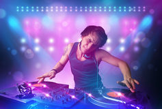 Disc jockey mixing music on turntables on stage with lights and stroboscopes. Young disc jockey mixing music on turntables on stage with lights and stroboscopes Stock Images