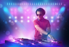 Disc jockey mixing music on turntables on stage with lights and Stock Photos