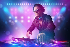 Disc jockey mixing music on turntables on stage with lights and. Young disc jockey mixing music on turntables on stage with lights and stroboscopes Stock Photos