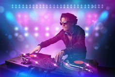 Disc jockey mixing music on turntables on stage with lights and Royalty Free Stock Photo