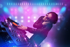 Disc jockey mixing music on turntables on stage with lights and Stock Image