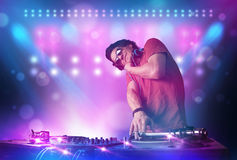 Disc jockey mixing music on turntables on stage with lights and Royalty Free Stock Images