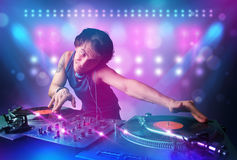 Disc jockey mixing music on turntables on stage with lights and Royalty Free Stock Photography