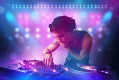 Disc jockey mixing music on turntables on stage with lights and Stock Images
