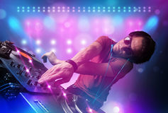 Disc jockey mixing music on turntables on stage with lights and. Young disc jockey mixing music on turntables on stage with lights and stroboscopes Royalty Free Stock Images
