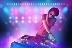Disc jockey mixing music on turntables on stage with lights and. Young disc jockey mixing music on turntables on stage with lights and stroboscopes Stock Photography