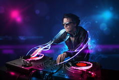 Disc jockey playing music with electro light effects and lights Royalty Free Stock Photo