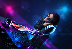Disc jockey playing music with electro light effects and lights. Young disc jockey playing music with electro light effects and lights stock images