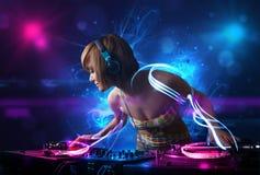 Disc jockey playing music with electro light effects and lights. Beautiful disc jockey playing music with electro light effects and lights royalty free stock image