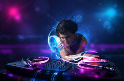 Disc jockey playing music with electro light effects and lights. Young disc jockey playing music with electro light effects and lights stock photo