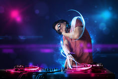 Disc jockey playing music with electro light effects and lights. Young disc jockey playing music with electro light effects and lights stock photography