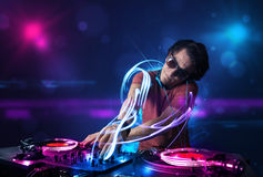 Disc jockey playing music with electro light effects and lights Stock Photos