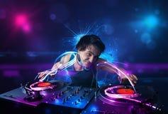 Disc jockey playing music with electro light effects and lights. Young disc jockey playing music with electro light effects and lights royalty free stock photos