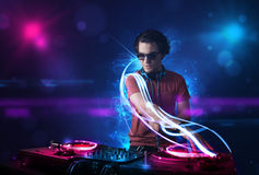 Disc jockey playing music with electro light effects and lights. Young disc jockey playing music with electro light effects and lights stock photos