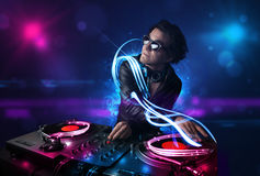 Disc jockey playing music with electro light effects and lights. Young disc jockey playing music with electro light effects and lights royalty free stock images