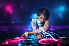 Disc jockey playing music with electro light effects and lights. Young disc jockey playing music with electro light effects and lights royalty free stock image