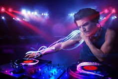 Disc jockey playing music with light beam effects on stage Royalty Free Stock Images