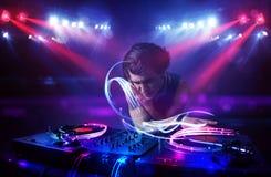 Disc jockey playing music with light beam effects on stage. Handsome disc jockey playing music with light beam effects on stage royalty free stock photography