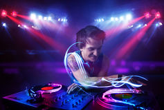 Disc jockey playing music with light beam effects on stage Stock Photography