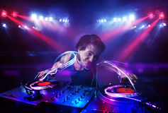 Disc jockey playing music with light beam effects on stage Royalty Free Stock Image