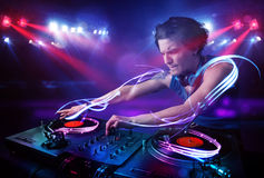 Disc jockey playing music with light beam effects on stage Royalty Free Stock Photography