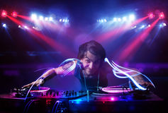 Disc jockey playing music with light beam effects on stage Stock Photos