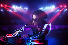 Disc jockey playing music with light beam effects on stage. Handsome disc jockey playing music with light beam effects on stage Royalty Free Stock Photo